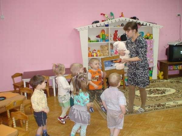 Воспитатель показывает детям игрушечного зайца