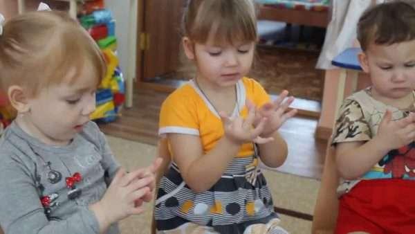 Трое детей выполняют пальчиковую гимнастику