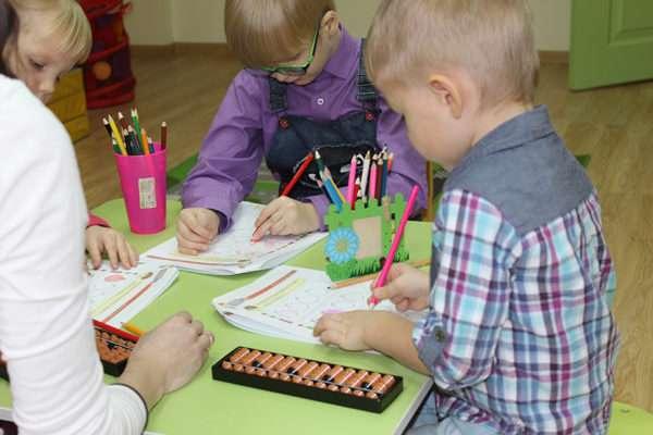 Дети за небольшим столом рисуют карандашами линии на листочках