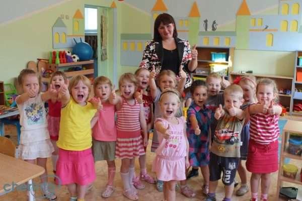 Радостные дети и воспитатель показывают большой палец
