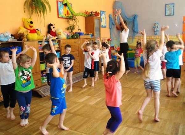 Дети, подняв руки, идут по кругу за педагогом