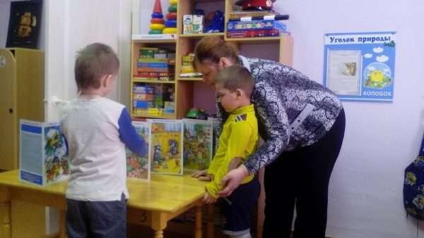 Воспитатель показывает детям книжки о профессиях