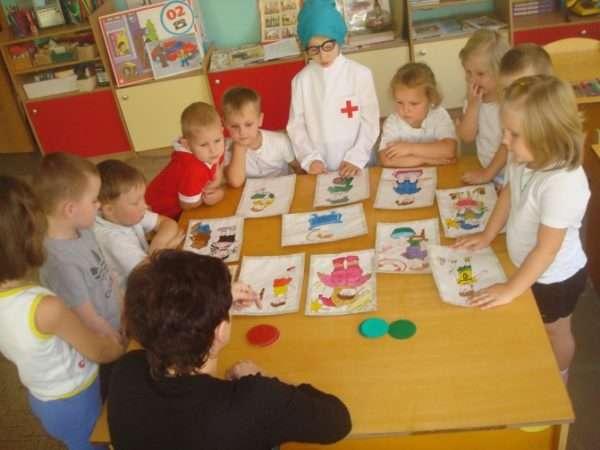 Дошкольники рассматривают картинки с изображёнными детьми