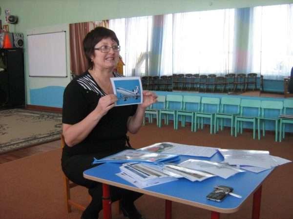 Воспитательница показывает картинку с изображением самолёта