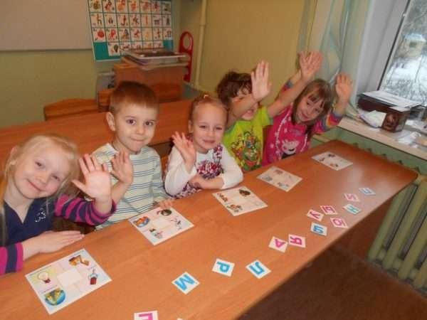 Пятеро детей за столом подбирают буквы к изображённым на карточках предметам