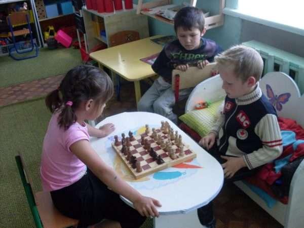 Мальчик и девочка играют в шахматы, а другой мальчик наблюдает