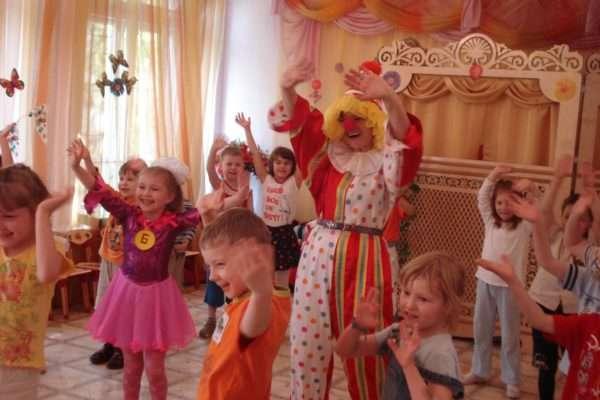 Дети и педагог в костюме клоуна улыбаются и машут руками