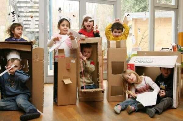 Семь ребят в разных позах в вырезанных картонных коробках