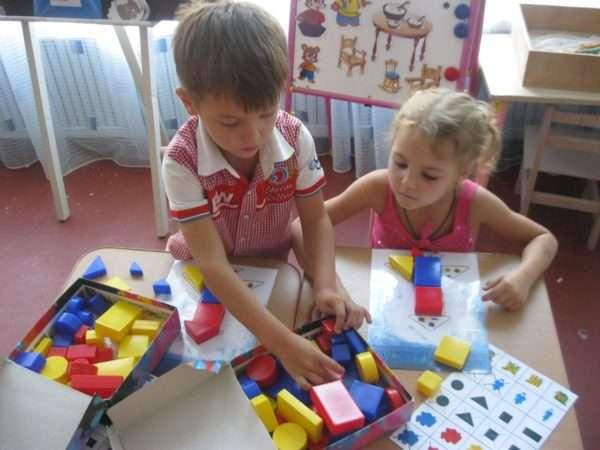 Мальчик и девочка составляют изображениеиз блоков по схеме