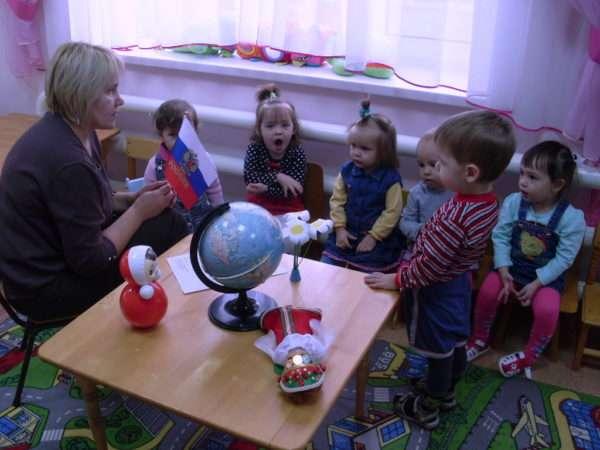 Педагог показывает детям флаг России