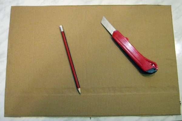 На листе плотного картона лежат карандаш и канцелярский нож