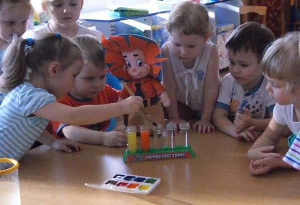 Дети стоят вокруг стола с водой и красками, рядом с ними кукла Незнайка