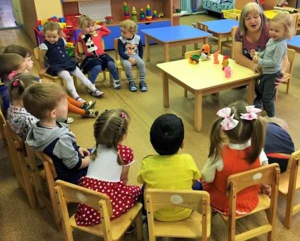 Дети сидят полукругом, педагог и девочка в центре