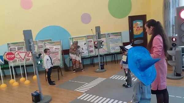 Ребёнок в синей шапке Незнайки стоит рядом с воспитательницей, на полу зала разметка пешеходного перехода, на заднем фоне Баба-Яга, мальчик в костюме регулировщика и что-то рассказывающий мальчик