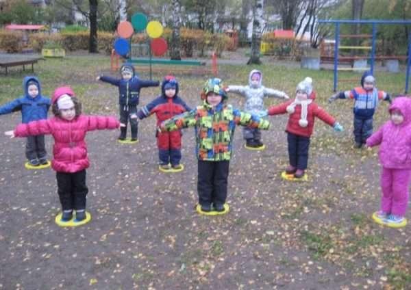 Дети на улице стоят в нарисованных кругах, расставив руки