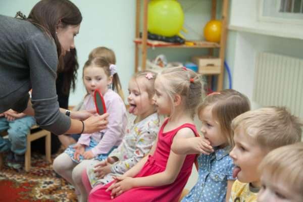 Дети по очереди показывают язык в зеркало, которое держит педагог