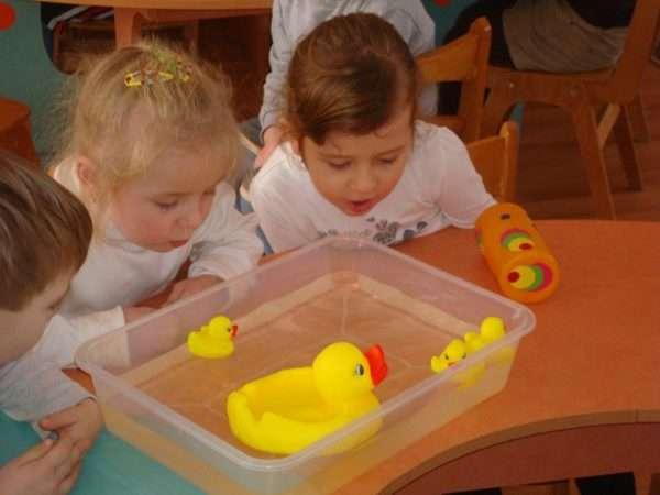 Дети дуют на резиновых уточек, плавающих в воде