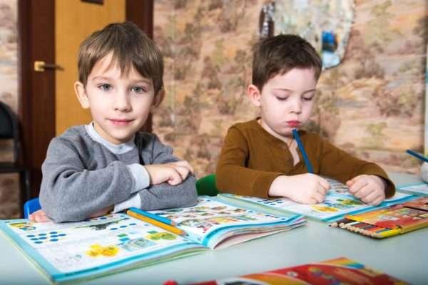 Два сидящих рядом мальчика работают с книгами