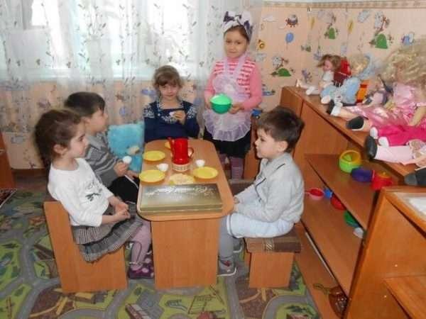 Дети сидят за столом с игрушечной посудкой