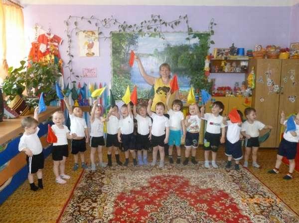 Дети с воспитательницей подняли флажки