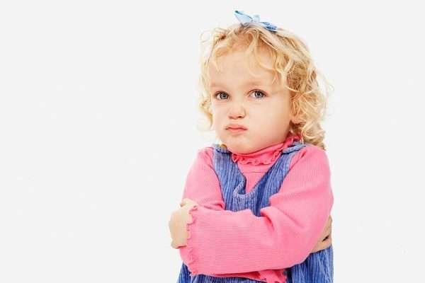 Обиженная девочка в розовой кофточке и сарафане обхватила себя руками