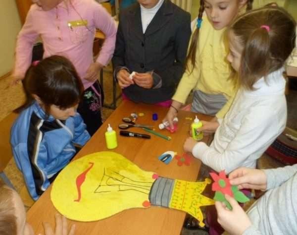 Дети работают над созданием большой лампочки из бумаги
