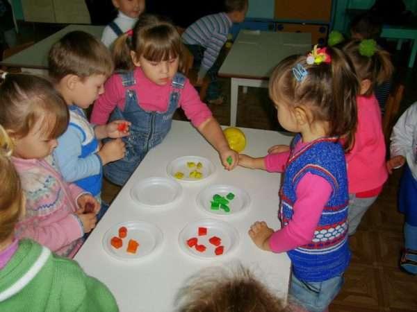 Дети стоят возле стола, на котором разложены кусочки разноцветного пластилина