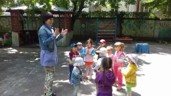 На прогулке воспитательница хлопает в ладоши, дети стоят в кругу, некоторые повторяют её движение
