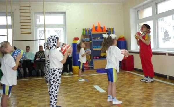 Дети играют в мяч с педагогом в костюме клоуна