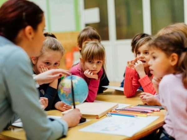 Педагог что-то рассказывает детям, показывая на глобус