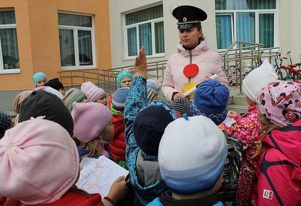 Воспитательница в образе светофора с детьми на улице