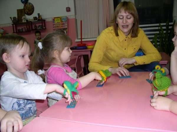 Воспитательница и дети барабанят пальчиками по прямоугольной выпуклой детали
