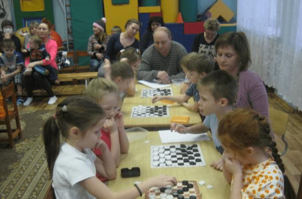 Дети играют в шашки в ходе турнира, родители наблюдают