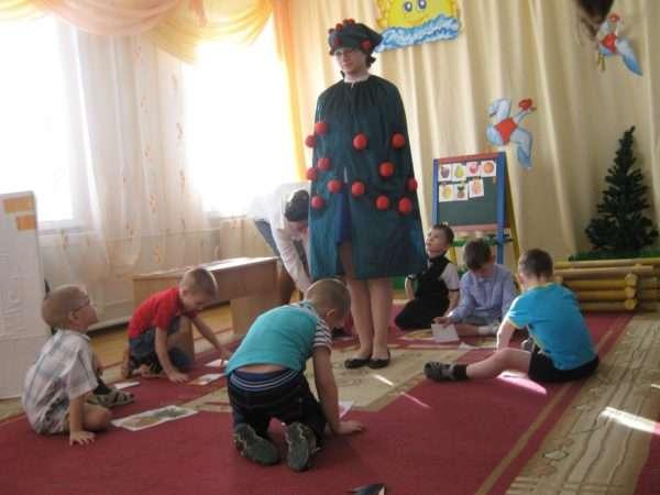 Дети сидят в кругу на ковре, перед ними лежат картинки с фруктами, в центре стоит педагог в костюме яблони