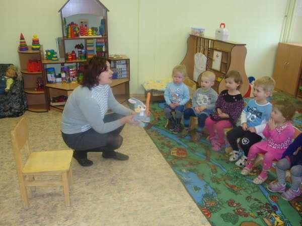 Воспитательница показывает детям игрушку-зайца