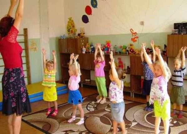 Дети и педагог стоят, подняв руки вверх