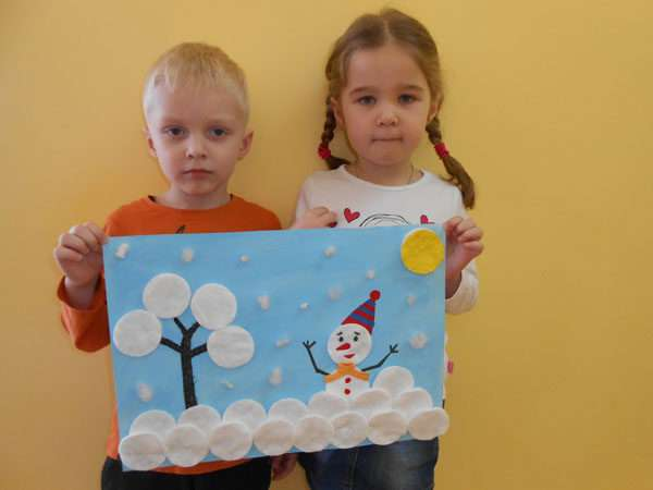 Мальчик и девочка держат аппликацию со снеговиком