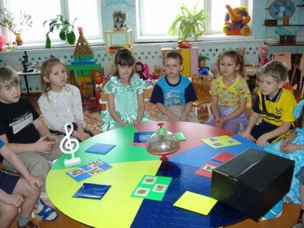Дети сидят за круглым столом, на котором разложены дидактические материалы