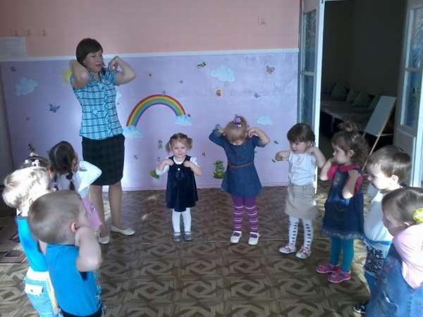 Дети и воспитательница, стоя в кругу, делают зарядку