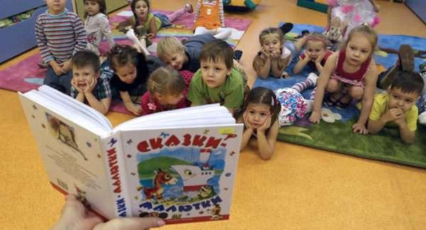 Дети, лёжа на полу, слушают сказку