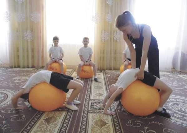 Дети занимаются на фитболах в зале