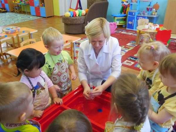 Воспитатель выпускает струйку воды из шприца, дети наблюдают
