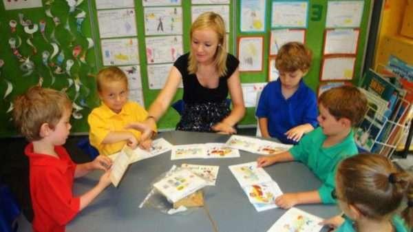 Дети и педагог сидят за столом, мальчик зачитывает текст с карточки