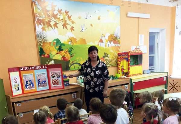 Воспитатель показывает детям буклет по безопасности