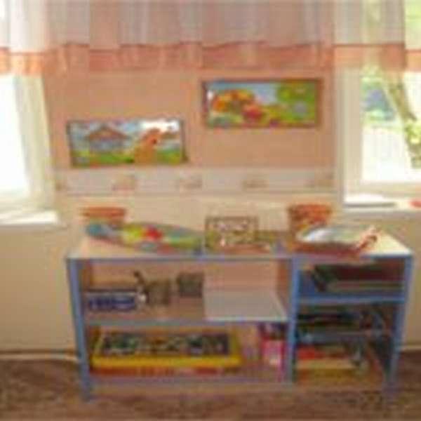 Стол с ящиками, заполненными материалами для творчества, на столе большая коробка с карандашами