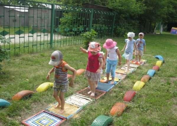 Дети на игровой площадке идут босиком по дорожке