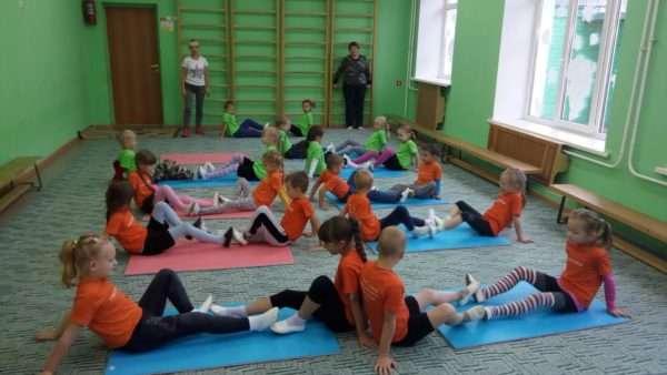 Дети выполняют упражнение на ковриках в спортивном зале