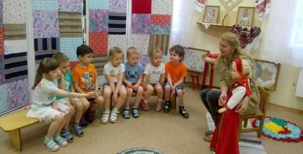 Воспитательница показывает детям куклу в красном сарафане