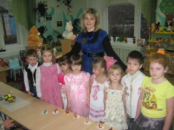 Педагог и группа детей стоят возле стола, на нём лежат вылепленные из пластилина герои сказок