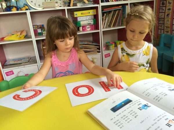 Две девочки рассматривают буквы Н, О, С
